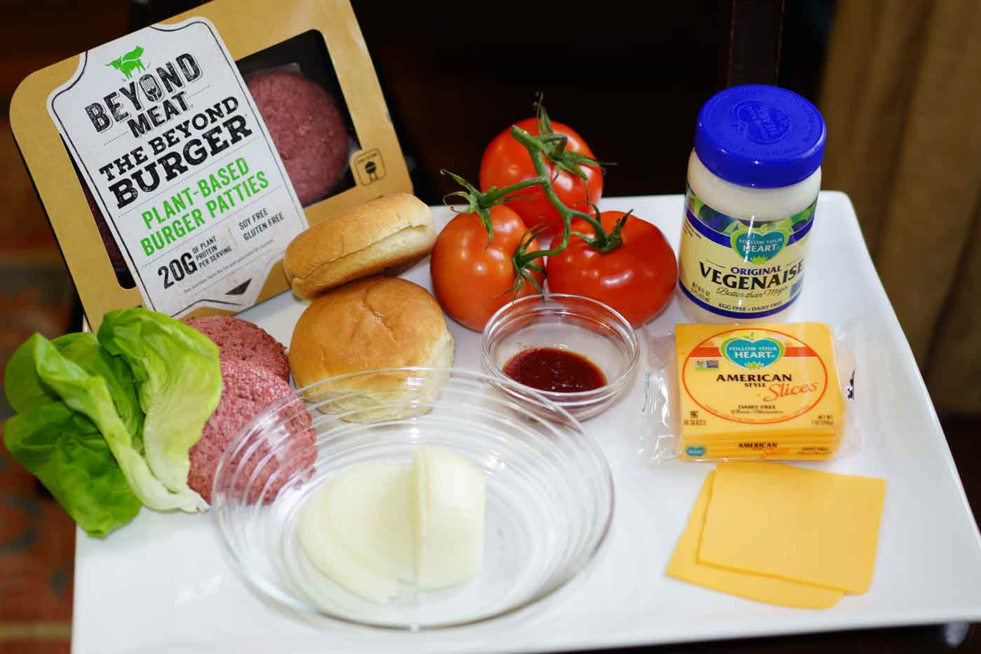 Beyond Burger vegan burger recipe condiments including vegenaise and follow your heart vegan cheese