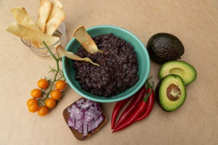 black bean recipe cooked up in a bowl with tomatoes red peppers avocado and red onion on the side for garnish