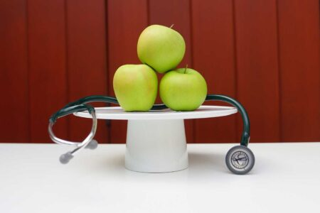 vegan health benefits three green apples on a pedestal with a stethoscope