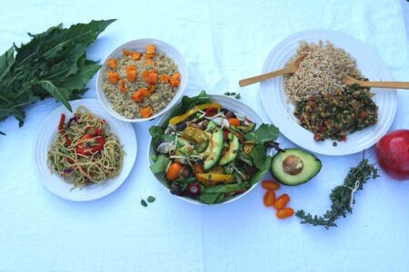 Table of healthy vegan food including a salad with seasoned tofu whole wheat pasta quinoa legumes and brown rice