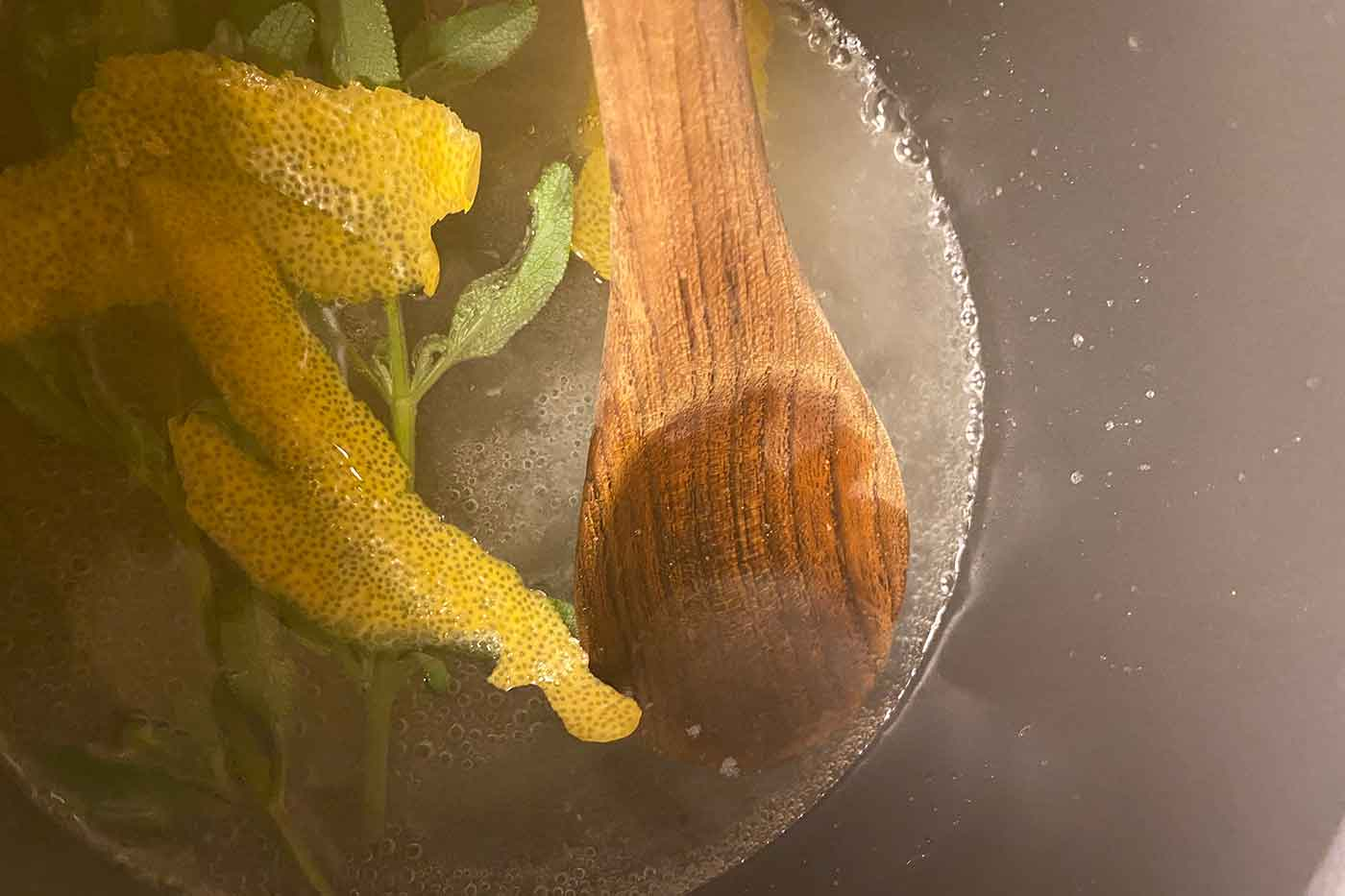 simple syrup cooking on the stove with lemon peel and sage to add to a cocktail recipe