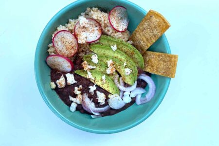 vegan burrito bowl with red onion avocado vegan Cotijo cheese radishes chips beans and brown rice