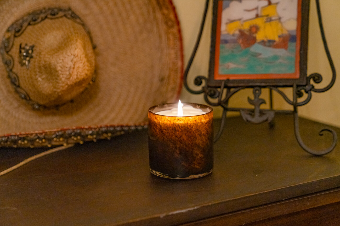 Redwood LAFCO candle pictured with a vintage Mexican hat and Spanish tile