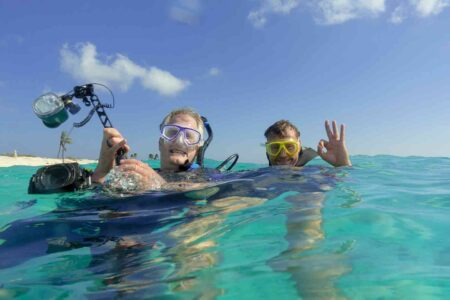 two scuba divers with cameras ready to descend Bonaire Island