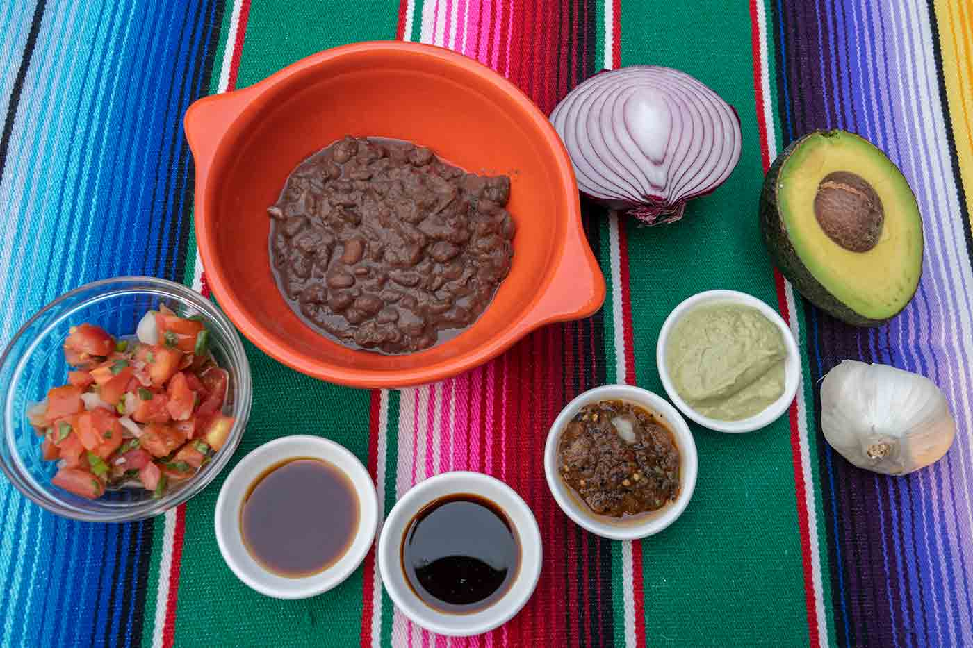 Tacodeli ingredients including beans soy sauce vinegar salsas and pico de gallo