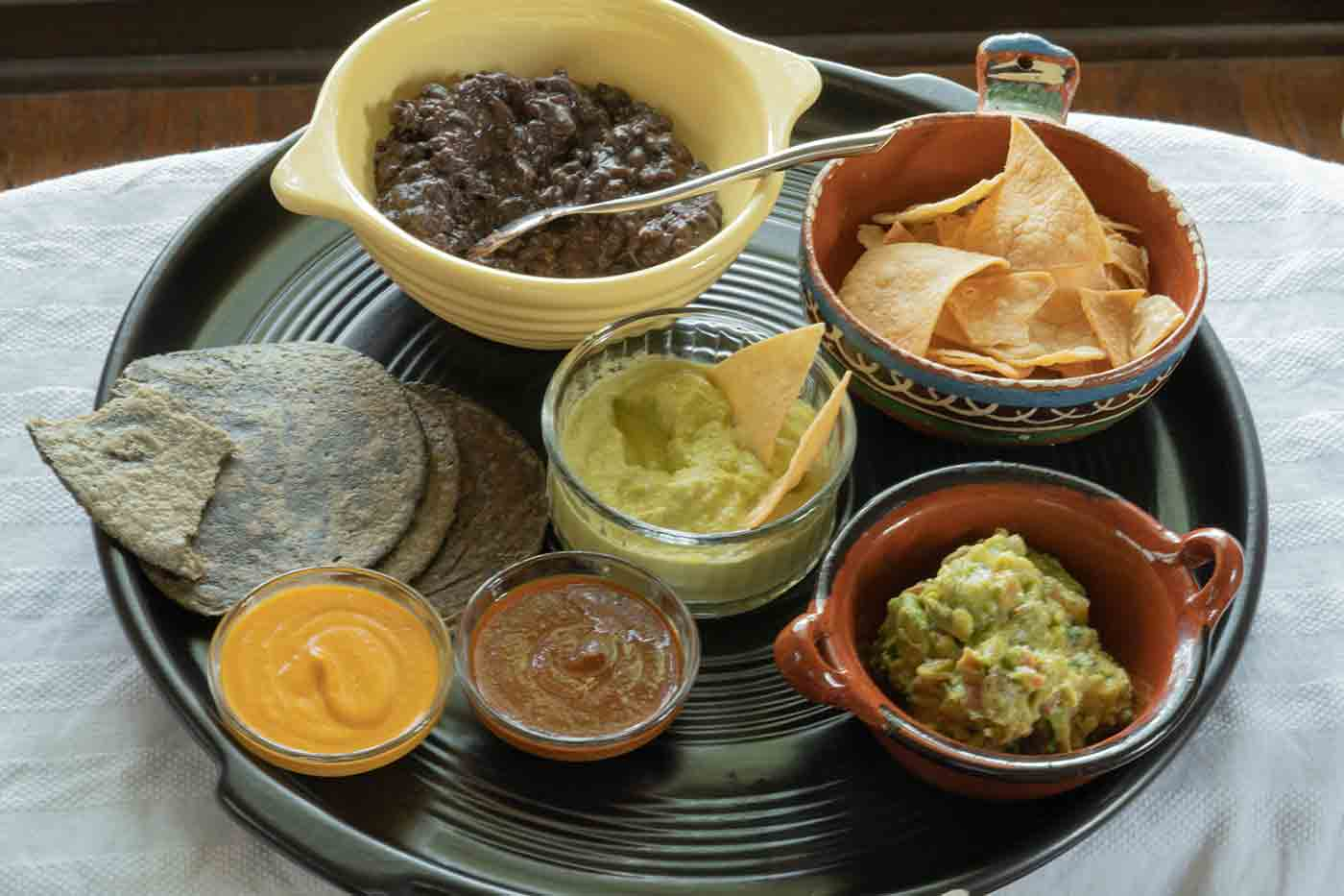 jalapeno sauce and other salsas with guacamole and beans and blue corn tortillas