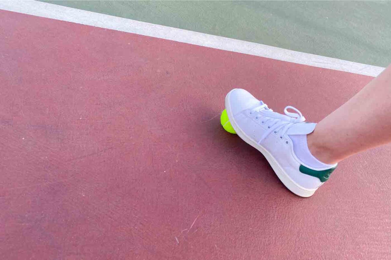 vegan Stan Smith tennis shoes from Adidas modeled on a tennis court with a tennis ball
